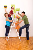 Happy family with painting utensils repainting their home — Stock Photo
