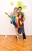 Happy family painting their new home together — Stock Photo