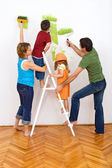 Happy family redecorating the house - painting — Stock Photo