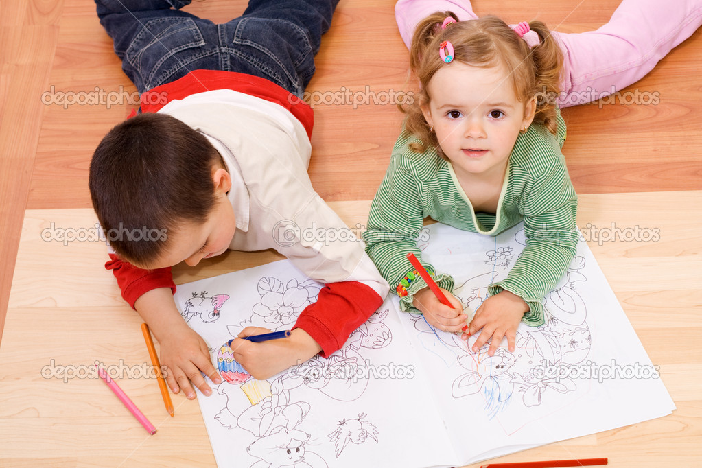 Kids coloring with colored pencils, laying on the floor — Stock Photo #6430076