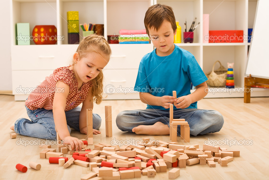 Little builders - boy and girl playing with wooden blocks — Stock Photo #6430221