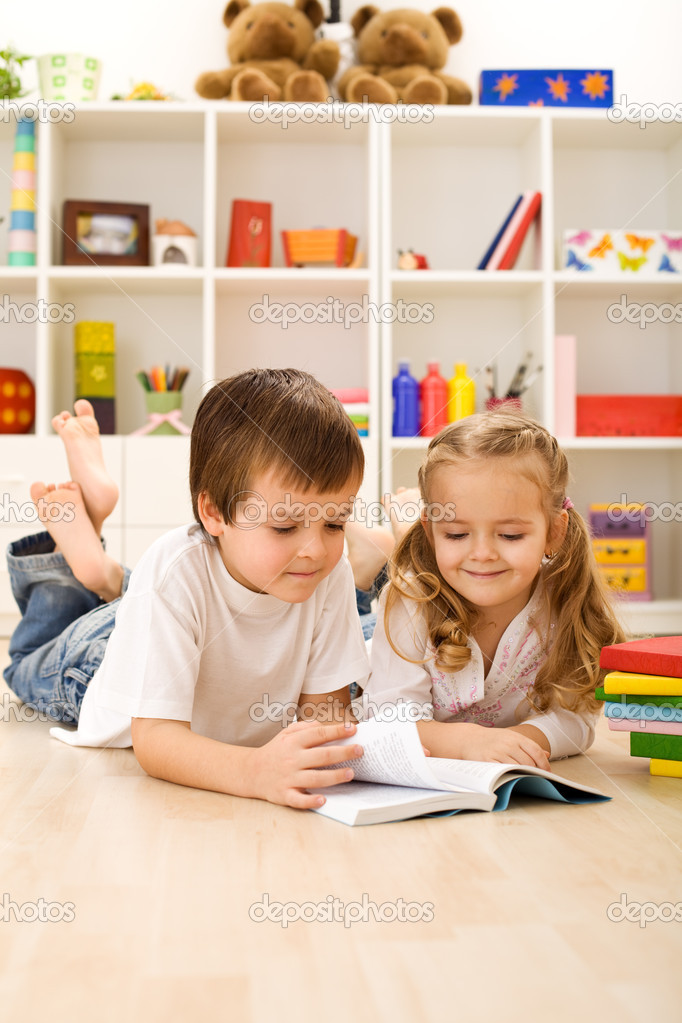 Little sister let me show you how to read - kids with books laying on the floor — Stock Photo #6430225