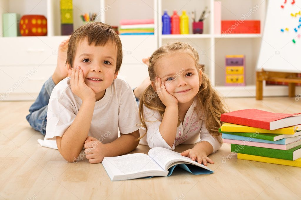 Happy kids with colorful books laying on the floor in their home — Stock Photo #6430239