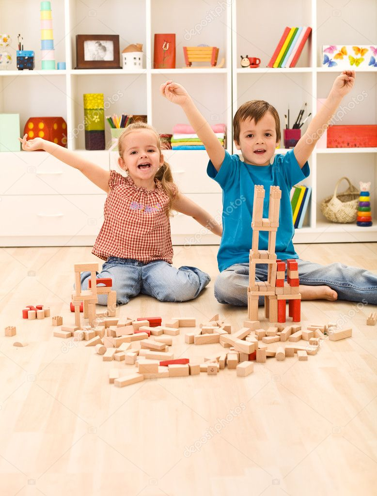 Kids proudly showing their wooden block buildings, sitting on the floor — Stock Photo #6430261