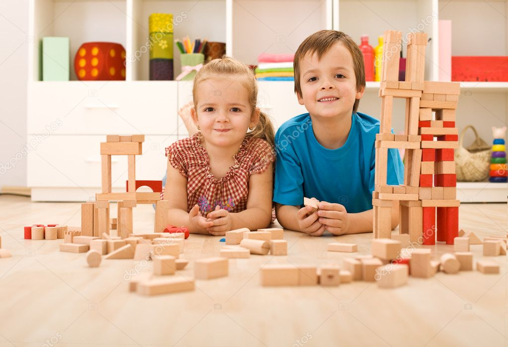 Happy kids with wooden blocks on the floor in their room  Stock Photo #6430263