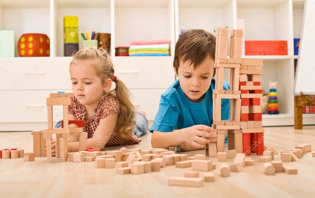 Kids playing with wooden blocks laying on the floor in their room — Stock Photo #6430266