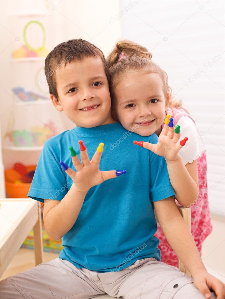Two happy kids in their room playing with game pieces fitting them on fingers — Stock Photo #6430350