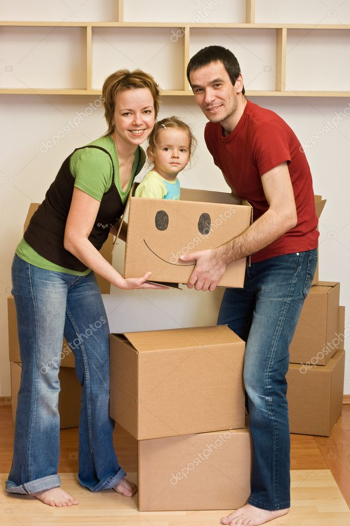 Happy family with a kid moving into a new home - lifting cardboard boxes — Stock Photo #6430394