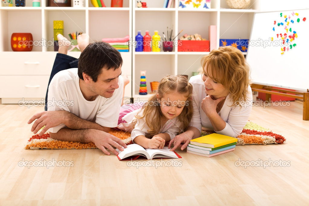 Happy family laying on the floor reading in the kids room — Stock Photo #6430449