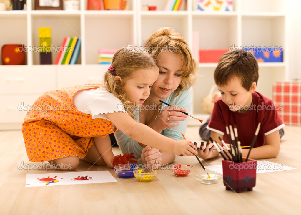Kids painting hands and making prints with their mother sitting on the floor — Stock Photo #6430600