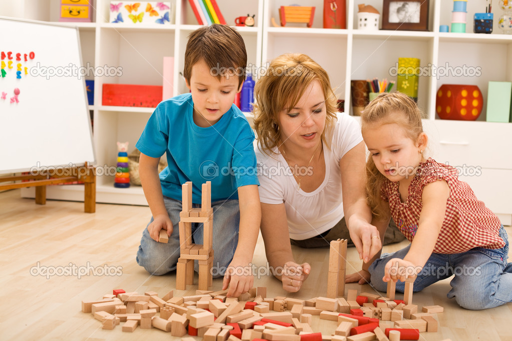 Woman and kids playing with wooden blocks laying on the floor  Stock Photo #6430601