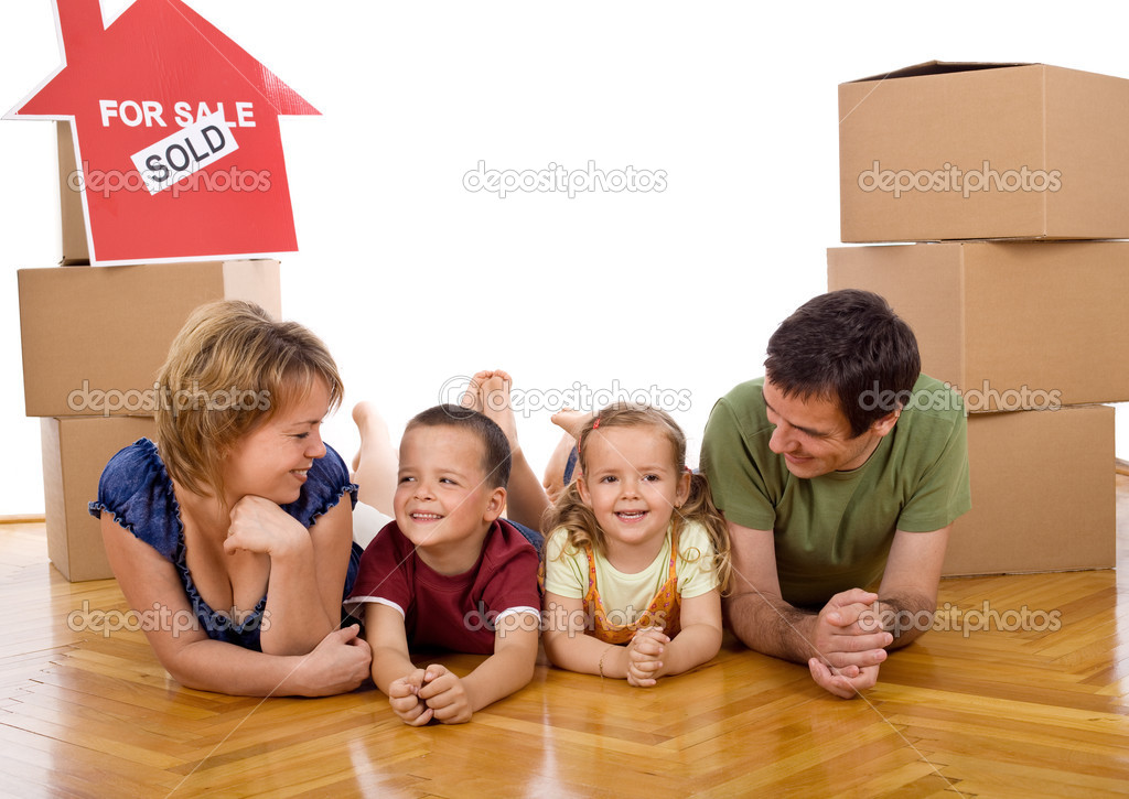 Happy family with two kids in their new home laying on the floor among cardboard boxes — Stock Photo #6430732
