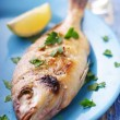 Fresh fish straight from the grill, in greek taverna setting - Stock Photo