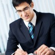 Portrait of writing smiling businessman working at office — Stock Photo #6304202