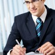 Portrait of writing smiling businessman working at office — Stock Photo #6304208
