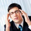 Thinking, tired or ill with headache businessman at office - Stock Photo