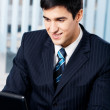 Successful happy smiling businessman working with laptop at offi — Stock Photo