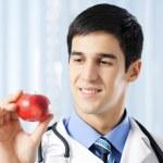 šťastné usmívající se doktor s apple, v kanceláři — Stock fotografie