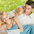 Young happy couple reading together newspaper outdoors — Stock Photo #6304953