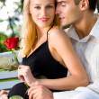Happy pregnant woman with rose and her husband, outdoors - Foto Stock