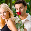 Stock Photo: Funny young happy couple with rosa, outdoors