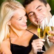Royalty-Free Stock Photo: Young couple celebrating with champagne together, outdoors