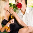 Stock Photo: Funny scene of couple celebrating with champagne and rosa, outdo