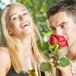 Royalty-Free Stock Photo: Young happy couple with champagne, gift and rose, outdoors