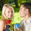 Young happy couple with champagne, gift and rose, outdoors — Stock Photo