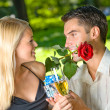 Stock Photo: Funny young happy couple with gift and rosa, outdoors