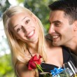 Young happy couple with gifts, rose and champagne outdoors — Stock Photo