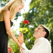 Funny young happy couple with rose, outdoors — Stock Photo #6305305