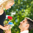 Young happy couple with rose and gift, outdoors — Stock Photo #6305309