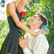 Funny young happy couple with gift and rose, outdoors — Stock Photo #6305314