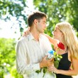 Young happy couple with gift and rose, outdoors — Stock Photo #6305318