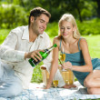young happy couple celebrating with champagne bei picknick — Stockfoto