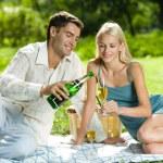 joven pareja feliz celebrando con champán en el picnic — Foto de Stock