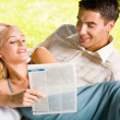 Happy smiling young couple reading together outdoors — Stock Photo