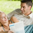 Young happy couple reading together newspaper outdoors — Stock Photo #6305490
