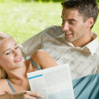 Young happy couple reading together newspaper outdoors - Stock Photo