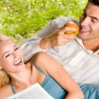 Young happy couple eating apples and reading newspaper outdoors - Stock Photo