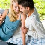 joven pareja sonriente con el portátil en el picnic — Foto de Stock
