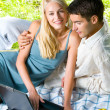 Young happy smiling couple with laptop at picnic — Stock Photo