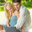 Young happy couple using laptop together, outdoors - Stock Photo