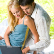 Young happy smiling couple with laptop at picnic — Foto Stock #6305527