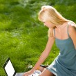 Young attractive blond woman on laptop outdoors — 图库照片
