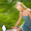 Young attractive blond woman on laptop outdoors — Stok fotoğraf