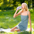 Young woman with bottle of water outdoors — Stockfoto