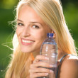 Foto Stock: Portrait of beautiful smiling woman with bottle of water, outdoo