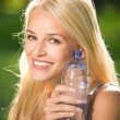 Stockfoto: Portrait of beautiful smiling woman with bottle of water, outdoo